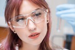 Skoncentrowany młody naukowiec trzyma próbnej tubki z odczynnikiem w chemicznym laboratorium w eyeglasses fotografia stock