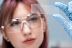 Skoncentrowany młody naukowiec trzyma szklanego mikroskopu obruszenie w chemicznym laboratorium w eyeglasses zdjęcie royalty free