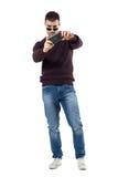 Skoncentrowany młody przypadkowy mężczyzna bierze obrazek z telefonem komórkowym obrazy stock