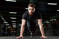 Skoncentrowany młody silny sporta mężczyzna robi desce ćwiczyć zdjęcie royalty free