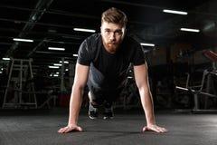 Skoncentrowany młody silny sporta mężczyzna robi desce ćwiczyć zdjęcie stock
