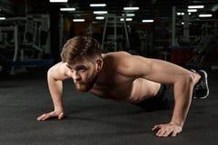 Skoncentrowany młody silny sporta mężczyzna robi sportowi ćwiczyć obrazy stock