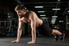Skoncentrowany młody silny sporta mężczyzna robi sportowi ćwiczyć zdjęcie royalty free