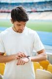 Skoncentrowany młody sporta mężczyzna patrzeje zegarek zdjęcia royalty free