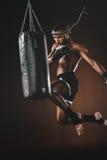 Skoncentrowany młody sportowa doskakiwanie i tajlandzki boks z uderzać pięścią torbę obraz royalty free