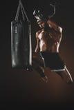 Skoncentrowany młody sportowa doskakiwanie i tajlandzki boks z uderzać pięścią torbę zdjęcie stock