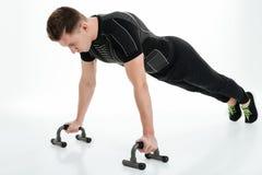 Skoncentrowany młody sportowiec podnosi z gym wyposażeniem robić pcha obraz stock