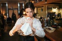 Skoncentrowany młody woamn wytarcia szkło Stoi przy barem i pracą zdjęcia royalty free