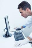 Skoncentrowany męski dentysta patrzeje komputerowego monitoru Obrazy Stock