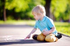 Skoncentrowany małe dziecko chłopiec obsiadanie i rysunek z barwioną kredą na asfalcie fotografia royalty free