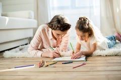 Skoncentrowany matki i córki rysunku obrazek w domu zdjęcie royalty free