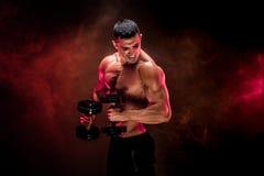 Skoncentrowany mięśniowy mężczyzna robi ćwiczeniu z dumbbell obrazy stock
