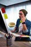 Skoncentrowany modnisia mężczyzna pracuje z audio słuchawki zdjęcia royalty free