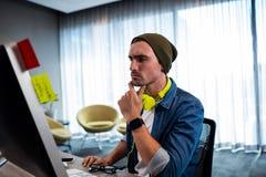 Skoncentrowany modnisia mężczyzna pracuje z audio słuchawki obrazy royalty free