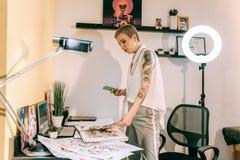 Skoncentrowany modny tatuażu artysta sprawdza jej albumy z nakreśleniami obraz stock