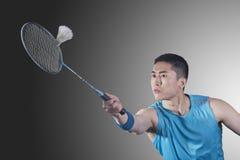 Skoncentrowany młody człowiek bawić się badminton, uderza Obrazy Royalty Free