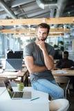 Skoncentrowany myślący młodego człowieka obsiadanie na stole w biurze zdjęcia royalty free