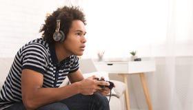 Skoncentrowany nastolatek bawić się gra wideo z joystickiem zdjęcia royalty free