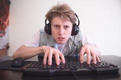 Skoncentrowany nastolatek w hełmofonach siedzi w domu w komputerowym pokoju i bawić się gra wideo fotografia stock