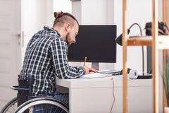 Skoncentrowany niepełnosprawny mężczyzna robi notatkom zdjęcie royalty free