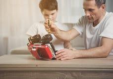 Skoncentrowany ojca naprawiania zabawki pojazd jego dziecko Obraz Stock