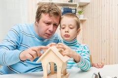 Skoncentrowany ojciec i syn buduje ptasiego dozownika Zdjęcie Royalty Free