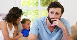 Skoncentrowany ojciec przed matki i syna obsiadaniem na kanapie zdjęcie wideo