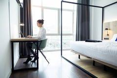 Skoncentrowany piękny bizneswoman pracuje z jej laptopem na biurku przy pokojem hotelowym zdjęcia stock