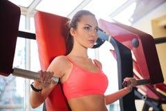 Skoncentrowany piękny młodej kobiety atlety szkolenie w gym obraz stock