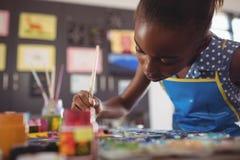 Skoncentrowany podstawowy dziewczyna obraz przy biurkiem zdjęcie royalty free