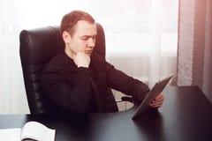 Skoncentrowany poważny biznesowy mężczyzna patrzeje jego ochraniacz obrazy stock