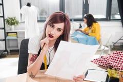 Skoncentrowany projektant mody patrzeje nakreślenie w ręce zdjęcia stock