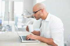 Skoncentrowany przypadkowy mężczyzna z filiżanką używać laptop w domu obrazy royalty free