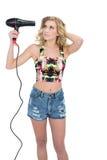 Skoncentrowany retro blondynka model używać włosianą suszarkę fotografia stock