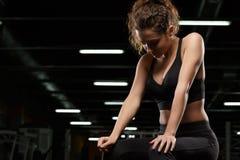 Skoncentrowany silny sport damy obsiadanie w gym zdjęcia royalty free