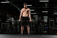 Skoncentrowany silny sporta mężczyzna robi sportów ćwiczeniom z barbell zdjęcie royalty free