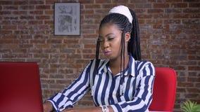 Skoncentrowany spojrzenie afrykański żeński patrzejący jej czerwonego laptop i wtedy rozczarowywający z fail znakiem zbiory wideo