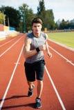 Skoncentrowany sporta mężczyzna bieg puszka stadium ślad z słuchawkami fotografia stock