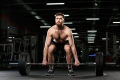 Skoncentrowany sporta mężczyzna robi sportów ćwiczeniom z barbell fotografia royalty free