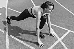 Skoncentrowany sportowy młody biegacz na zaczyna linii przy bieg śladu stadium Obrazy Royalty Free