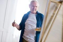 Skoncentrowany starszego mężczyzna rysunku obrazek w sztuka warsztacie zdjęcie royalty free
