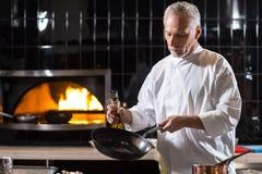 Skoncentrowany starzejący się szefa kuchni kucharstwo w restauraci zdjęcie stock