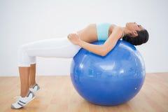 Skoncentrowany stonowany kobiety szkolenie na sprawności fizycznej piłce obraz stock