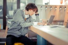 Skoncentrowany studencki działanie na jego dyplomówce w kawiarni obrazy royalty free