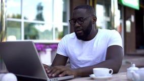Skoncentrowany studencki działanie na uniwersyteckim projekcie używać laptop, siedzi w kawiarni fotografia stock