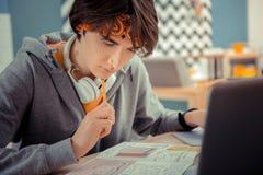 Skoncentrowany studencki główkowanie na jego trudnym hometask zdjęcie stock