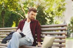 Skoncentrowany studencki studiowanie z laptopem i notatnikiem outdoors zdjęcie royalty free