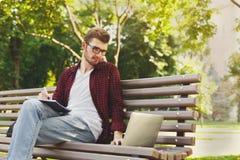 Skoncentrowany studencki studiowanie z laptopem i notatnikiem outdoors fotografia royalty free