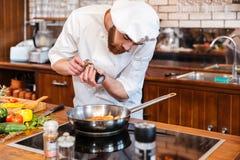 Skoncentrowany szefa kuchni kucharz gotuje łososiowego stek na smażyć nieckę fotografia stock