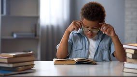 Skoncentrowany szkolny uczeń czyta literaturę w bibliotece w eyeglasses, głupek chłopiec obraz stock